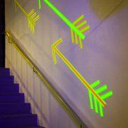 Neon arrows under blacklight directional signage