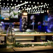Communal farm tables under string bulb lights